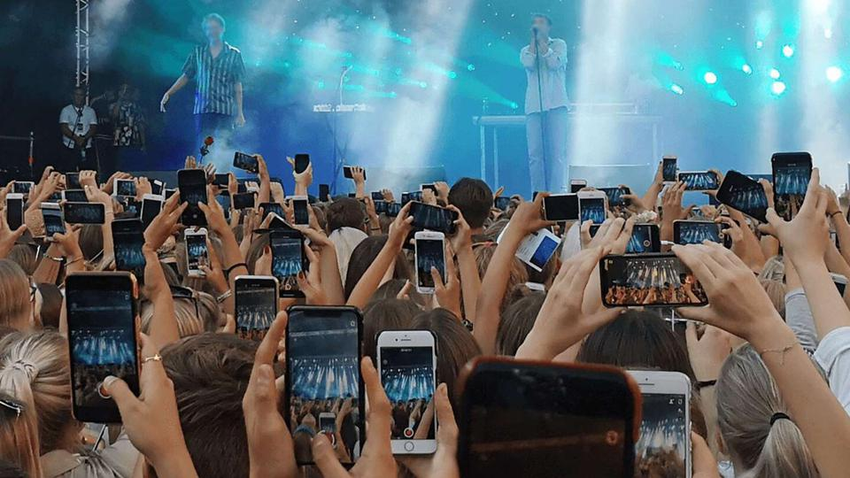 Fans with smartphones at an outdoor concert.