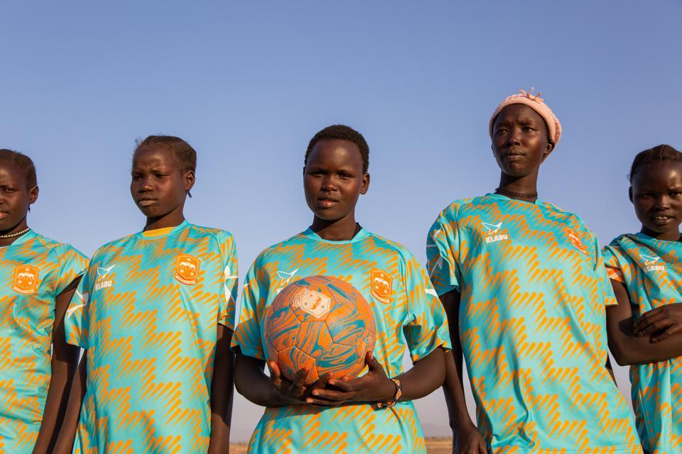 Members of Kalobeyei sports club in Kalobeyei Spirit home shirts.