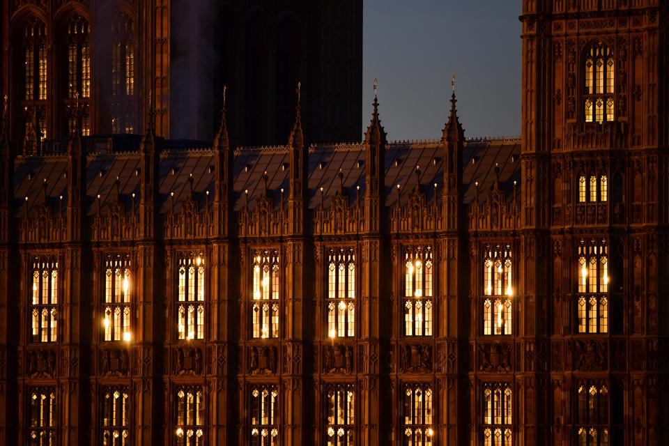 Light illuminates windows in the Houses of Parliament in the early morning in London