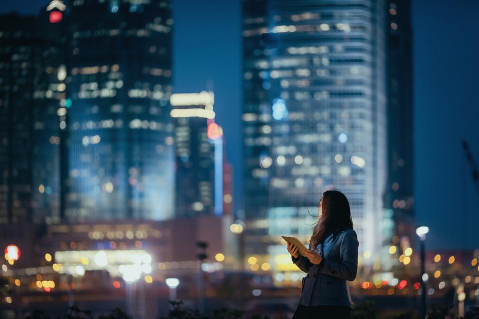 Young businesswoman using digital tablet, looking back over illuminated city skyline with confidence at night