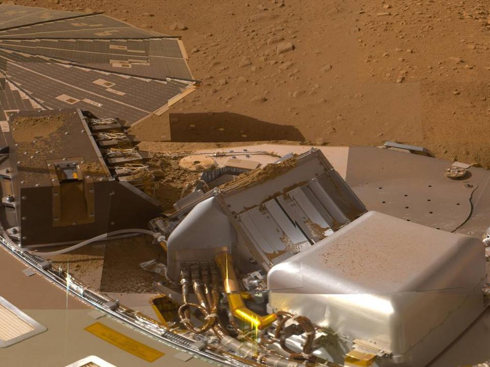 Photo of Phoenix lander's deck, with reddish Martian ground in background.