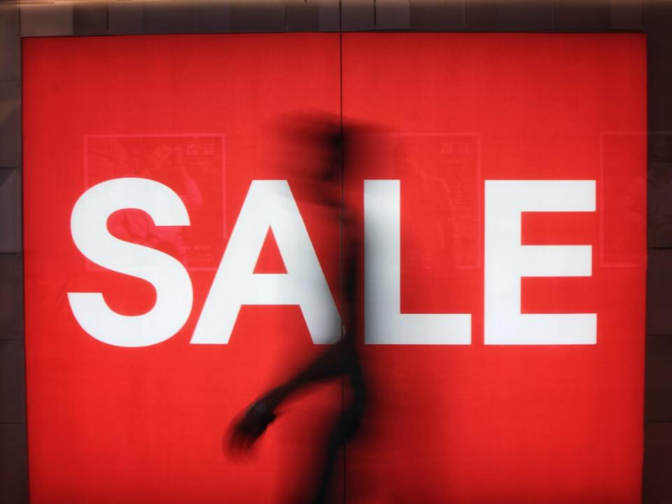 A sale sign with a passerby ...