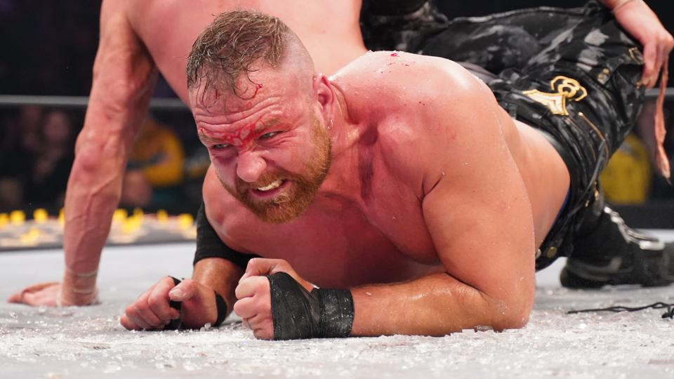 Jon Moxley, trapped in Kenny Omega's scorpion hold, crawls through glass to make it to the ring ropes at AEW Full Gear in Baltimore on November 9, 2019.