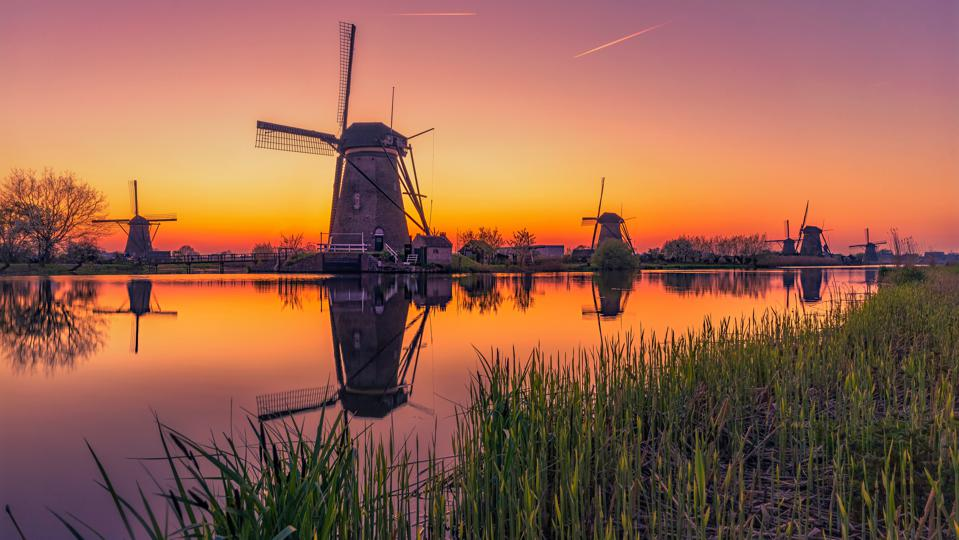 Traditional Windmills Against Sky During Sunset