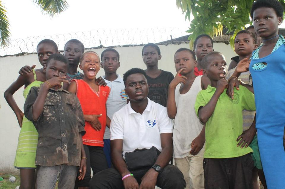 James Okina, founder of Street Priests, with kids who need help