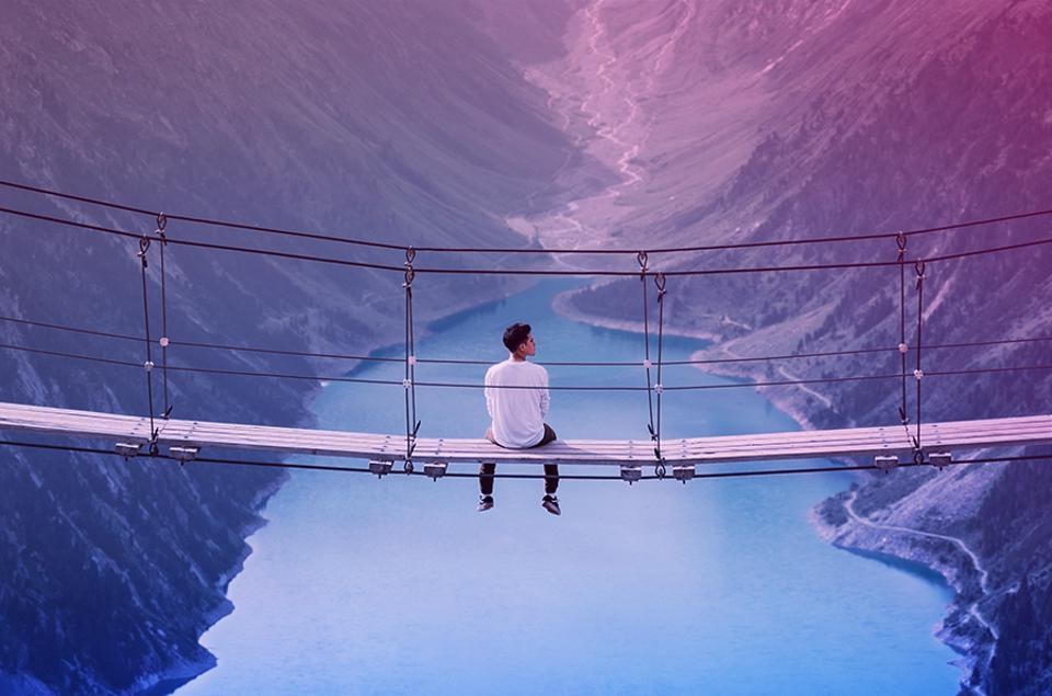 Man sits on bridge looking at beautiful valley