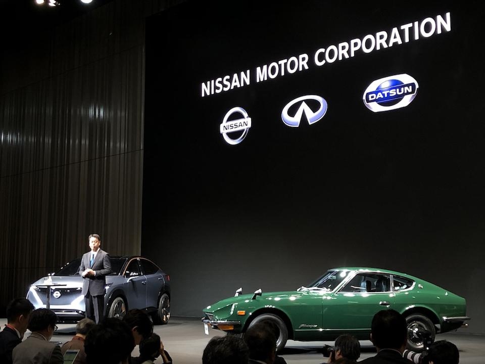 New CEO Makoto Uchida stands in front of a 1969 240Z and a new electric Ariya concept car.