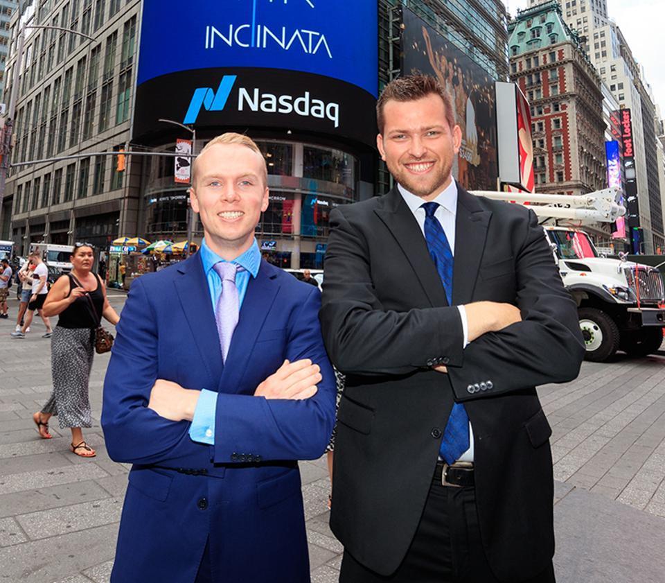 Vita Inclinta cofounders Derek Sikora and Caleb Carr both stand in front of Nasdaq.
