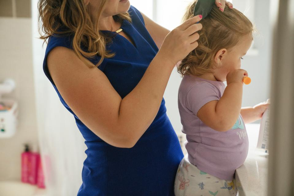 Working Mom brushing her young daughter's hair while she brushes her teeth.