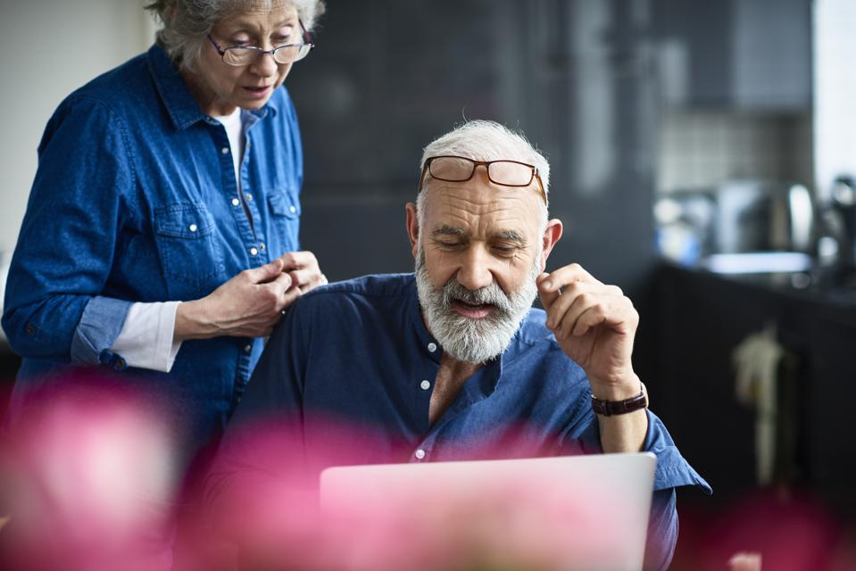 Hipster senior man with beard using laptop and woman watching