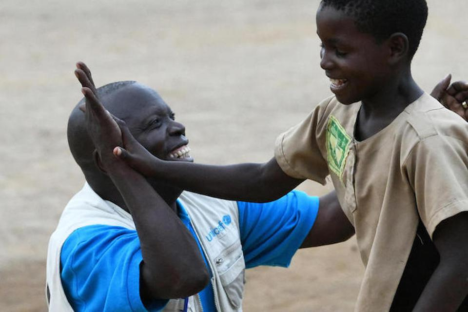 UNICEF staff member Jean Marie Samuel Ouenabio high-fives a young student in the south of Congo in 2019.