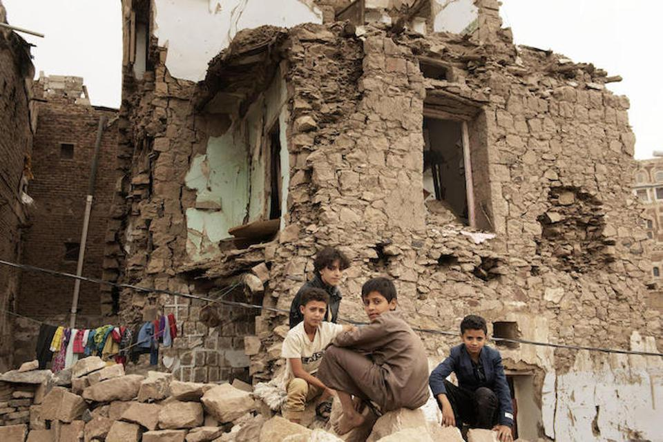 Children sit in front of a house that was damaged by an air strike in Sana'a, Yemen in July.