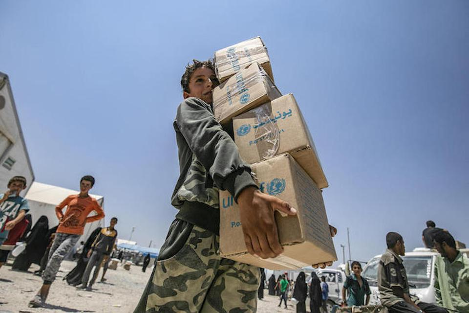 On July 22, 2019, a young boy collects a UNICEF-supported summer clothing kit at Al Hol refugee camp, south of Hasakeh City, Syria