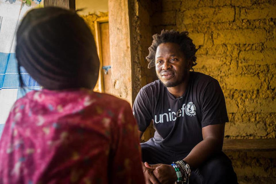 Ishmael Beah talks with 8-year-old Adama*, who was sexually abused by a teacher at her school in Sierra Leone's Tonkolili district.