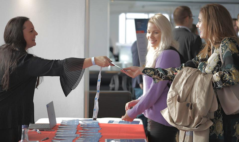 A woman handing a lanyard to another female.