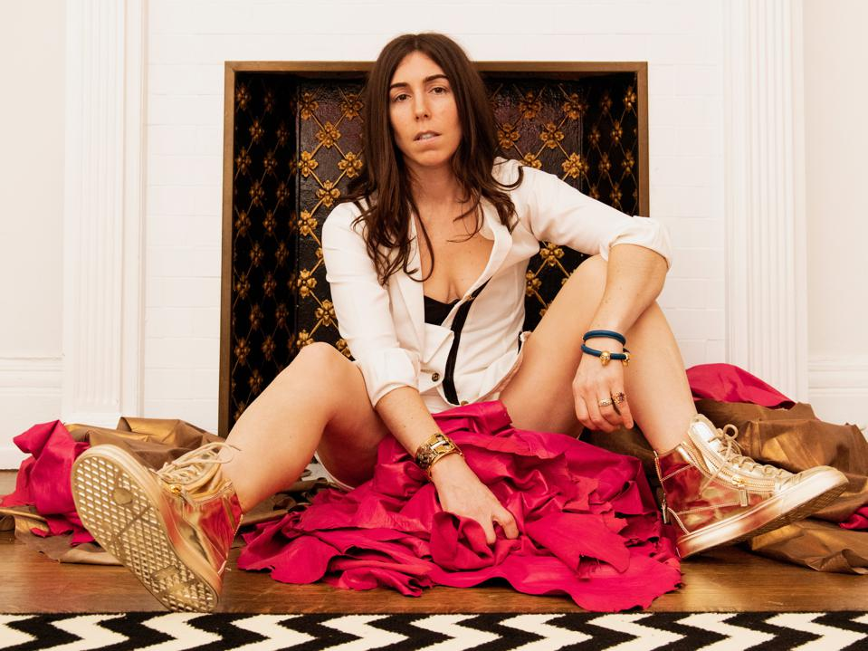 Stephanie Benedetto sits on a black-and-white checked floor on a heap of red fabric.