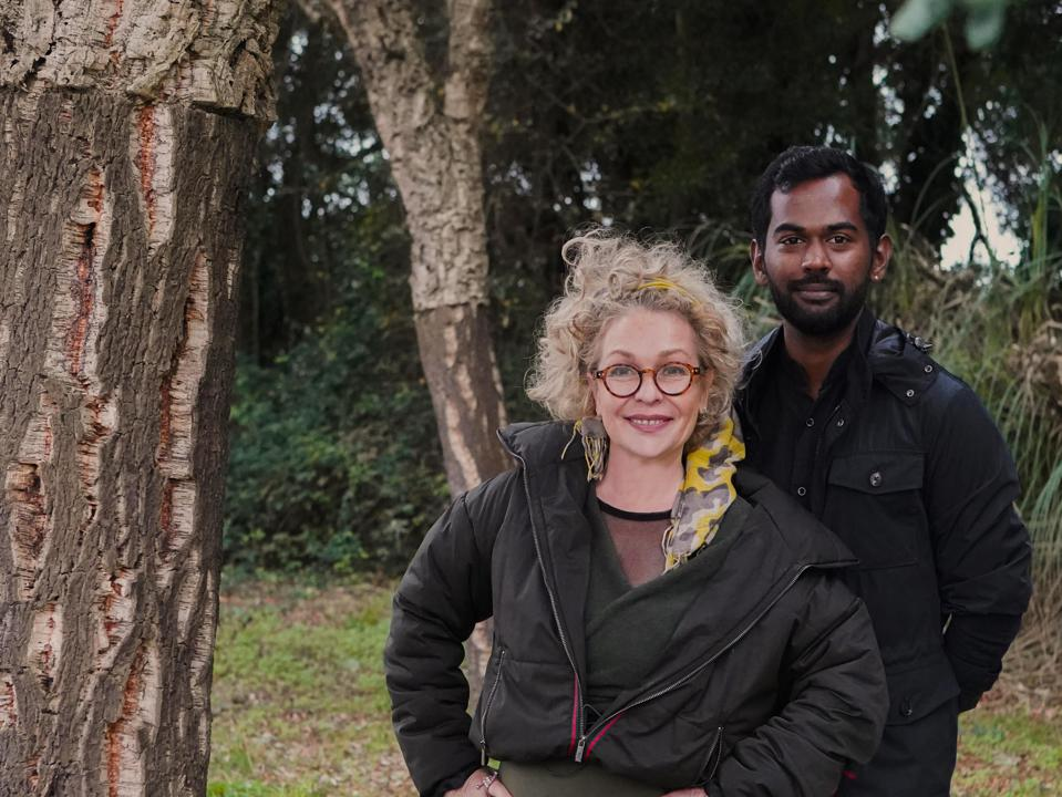 Marina Shtatlender and Gero Francis stand in a field with cork trees around them.