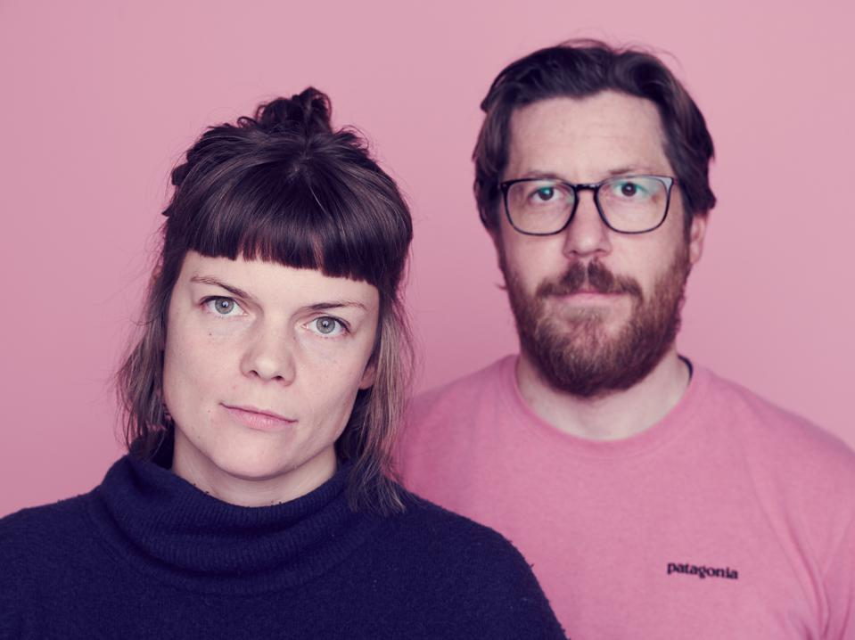Lucy Greenwood and Chris Renwick stand in front of a pink background.