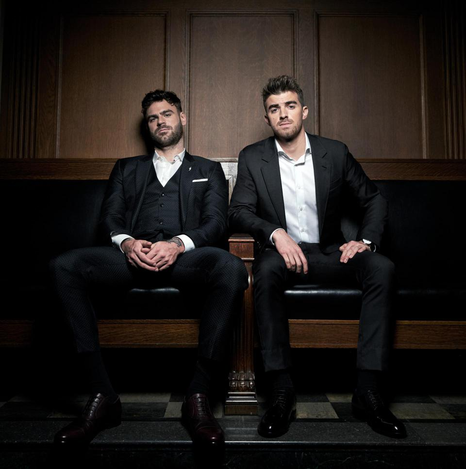 The Chainsmokers DJ duo Alex Pall and Drew Taggart are sitting and posing for a photo while wearing suits.