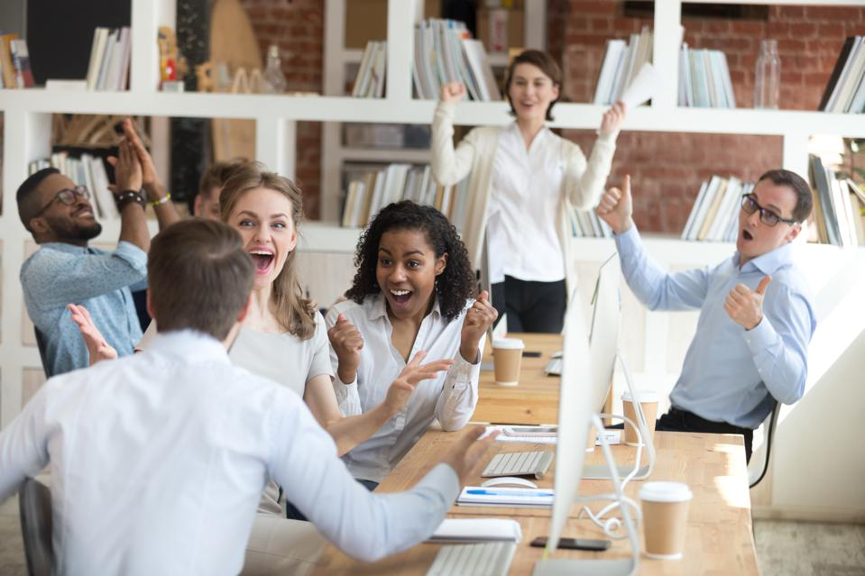 Male employee shares good news with excited diverse colleagues