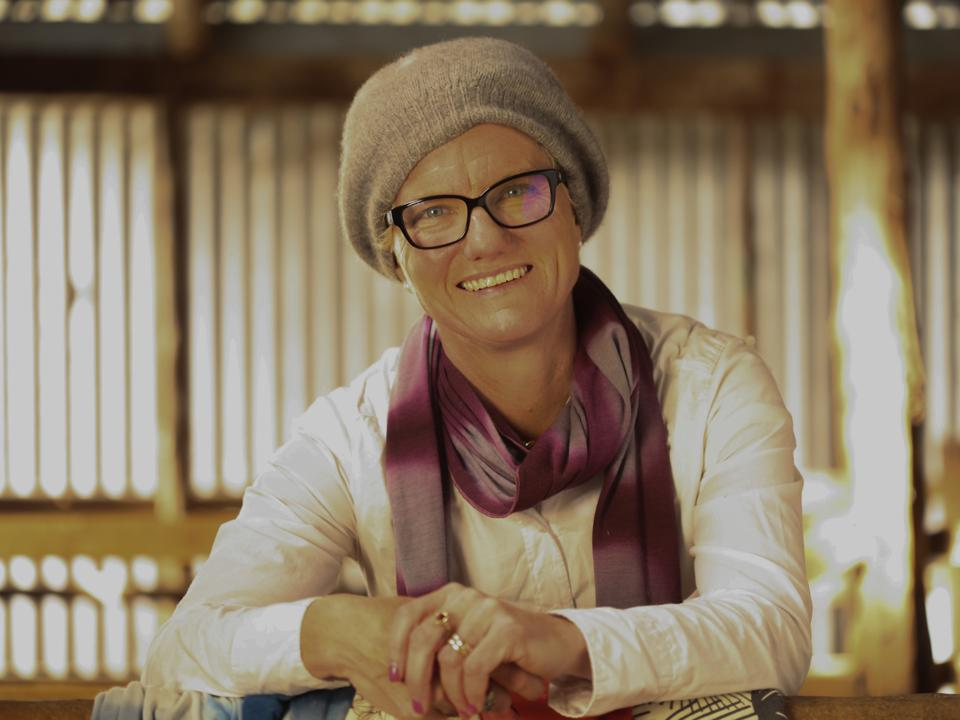 Pip Smith poses in a hat, black-framed glasses and scarf.