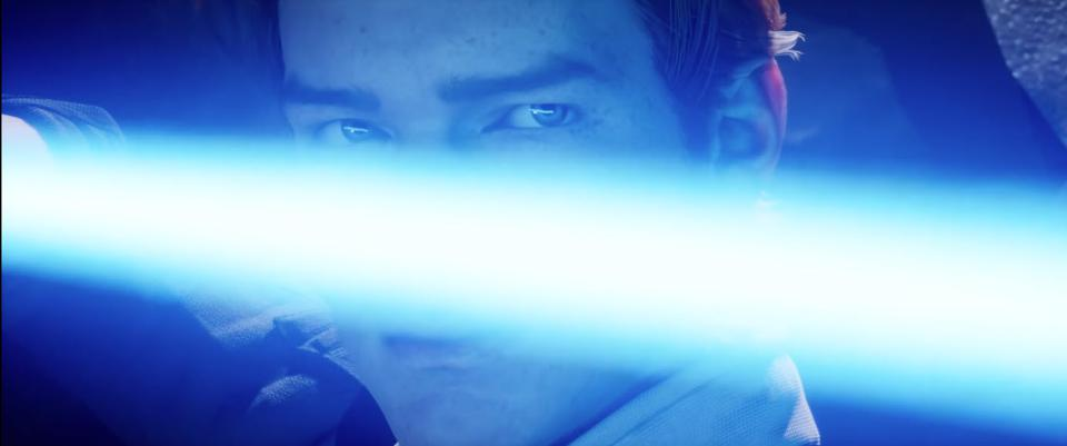 Close up of character's face partially covered by a lightsaber