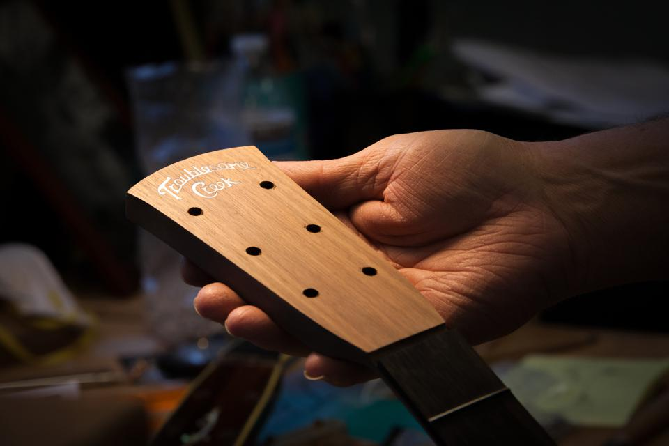 Doug Naselroad, of the Appalachian Luthiery School, hold a partially made guitar head with the Troublesome Creek logo.