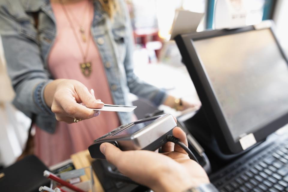 Female shopper paying with contactless credit card in shop