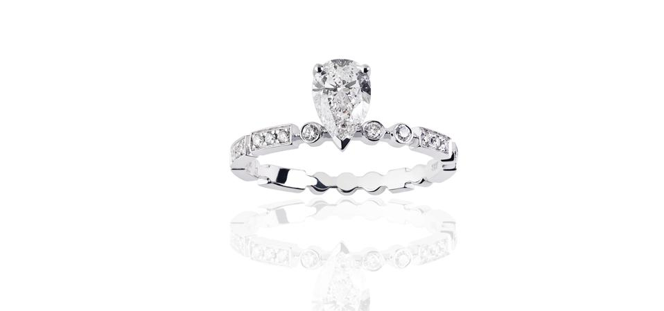 18ct white gold engagement ring by Hint, with brilliant and baguette-cut diamonds and a central pear-cut diamond, price on application.