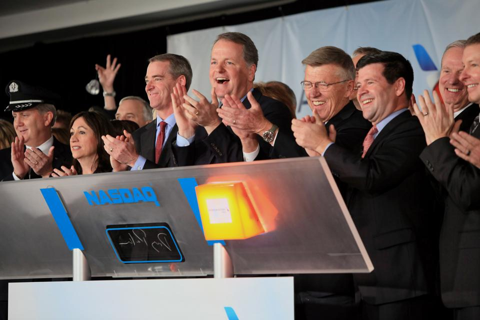 Doug Parker, Bob Crandall, and Scott Kirby (far right) applaud as American Airlines is listed on NASDAQ