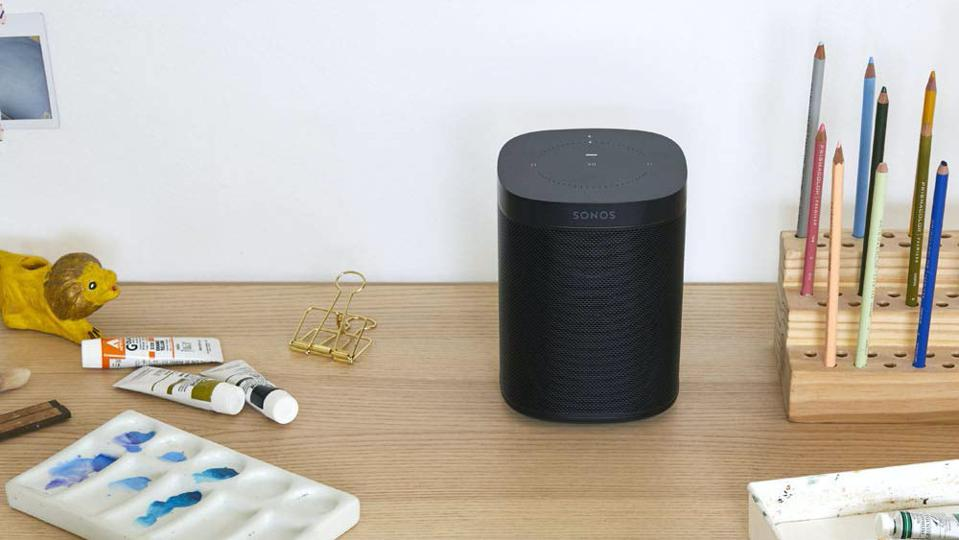 Black Sonos One speaker on a table.
