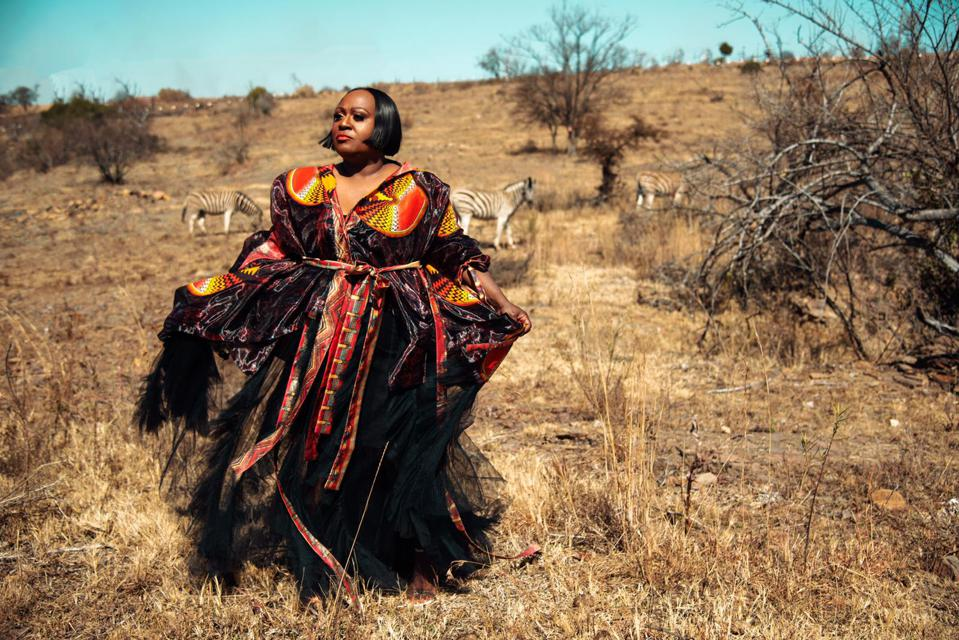 A woman in a ball gown poses in the savannah with zebra in the background.