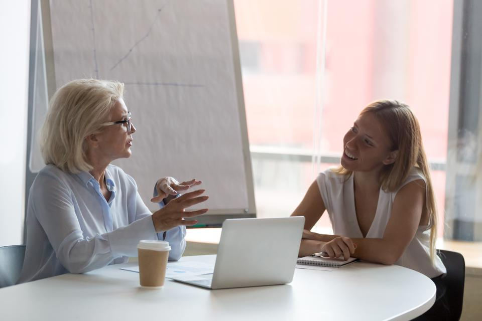 Mature businesswoman mentor talking with female intern in boardroom