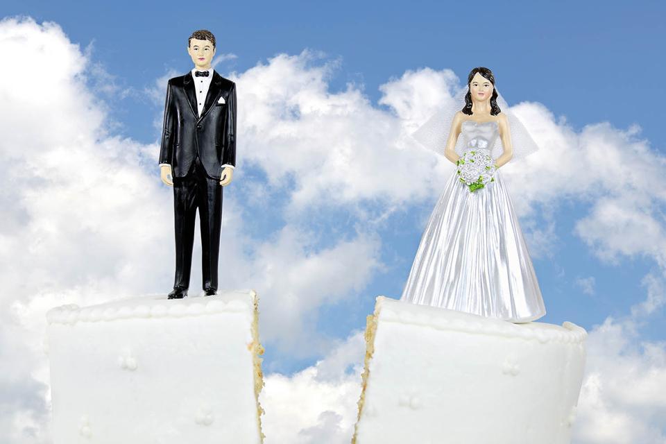 Bride and groom atop a split divorce cake