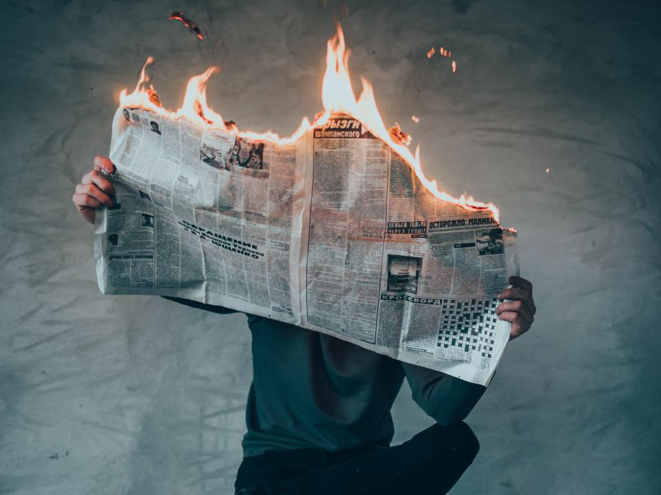 Man with newspaper on fire