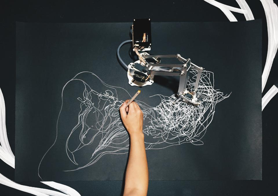 A hand drawing on a canvas alongside robotic arm