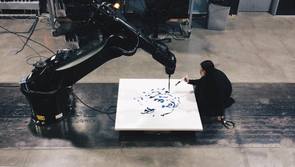 An artist painting on white canvas with large robotic arm