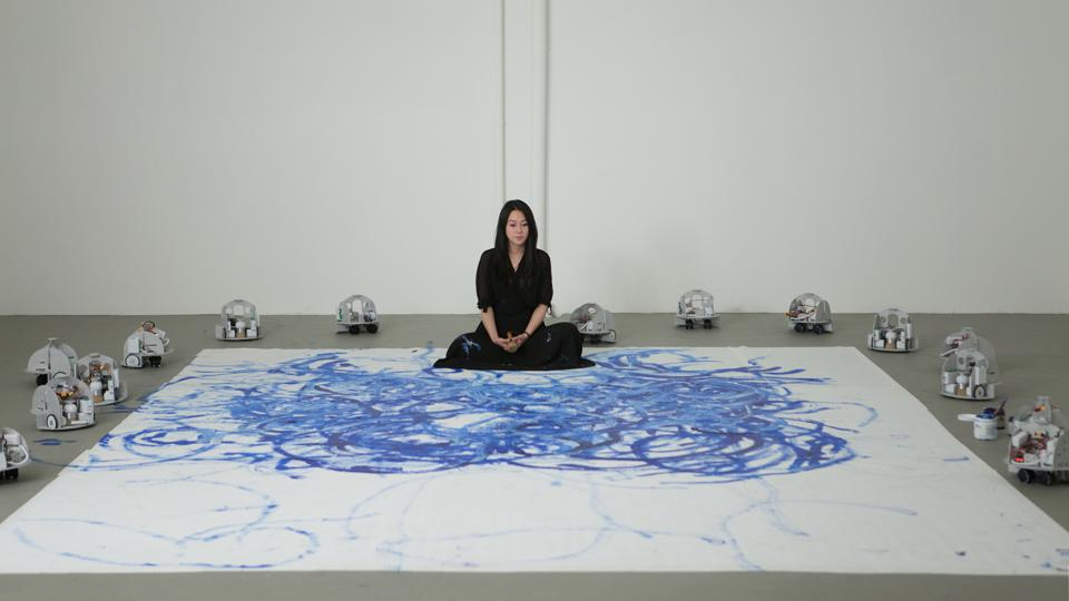An artist sitting on the floor at the top of large canvas