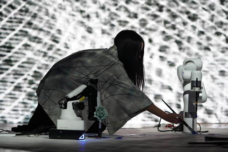 An artist in a dark room painting alongside one small robotic arm