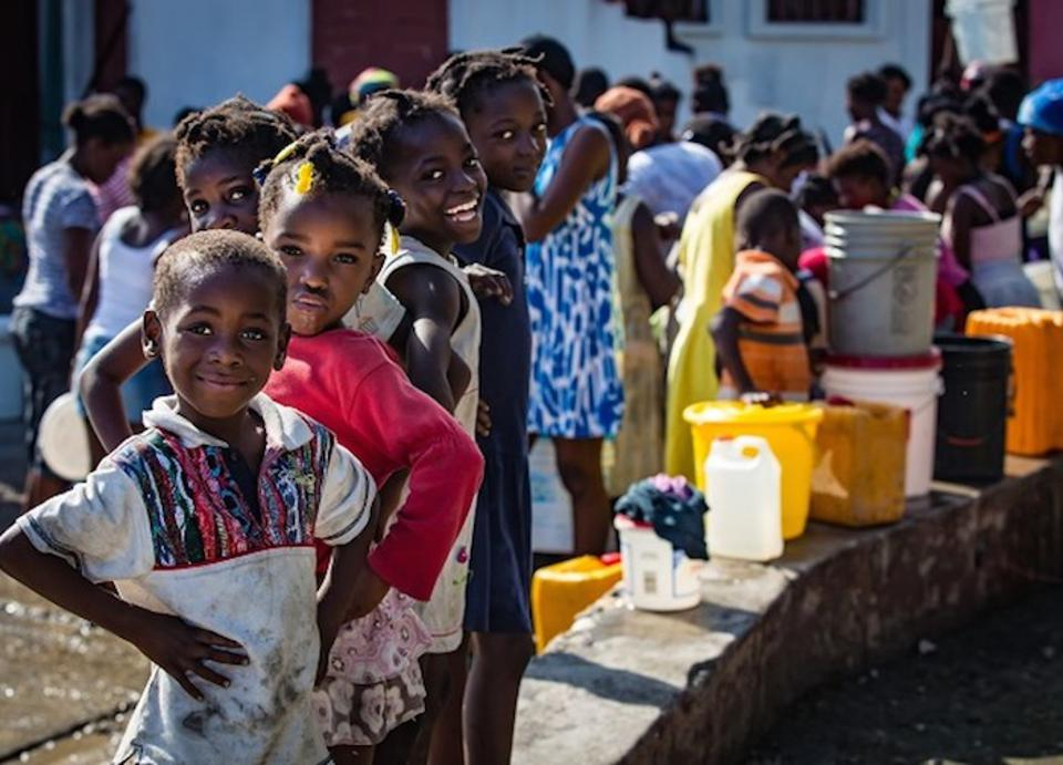 Kids in Haiti collect safe water at a UNICEF distribution point following Hurricane Matthew, which disrupted supplies and put families at risk of cholera and other waterborne diseases.