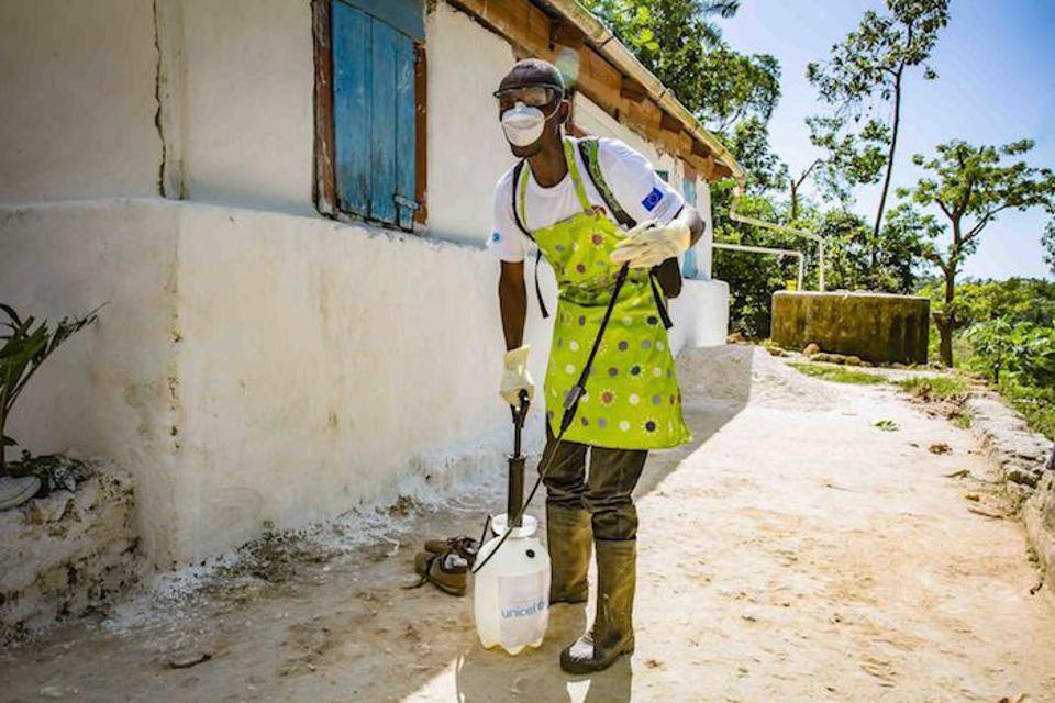 A member of a cholera rapid response team in Haiti prepares to disinfect a residential area suspected of being contaminated with disease-causing bacteria.