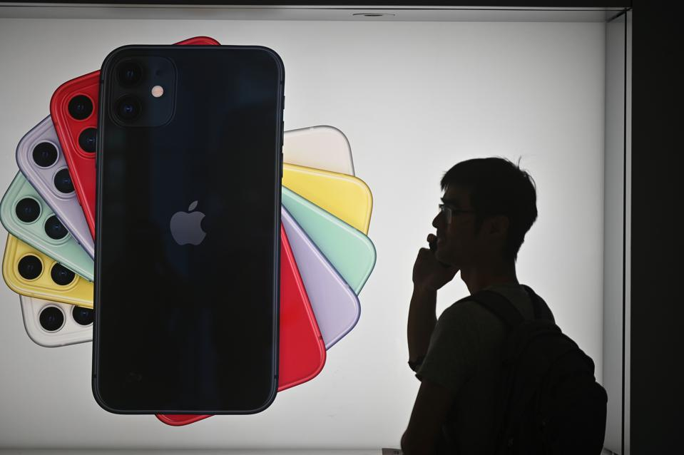 Large wall ad of several iPhones, with a man in shadow talking on his phone