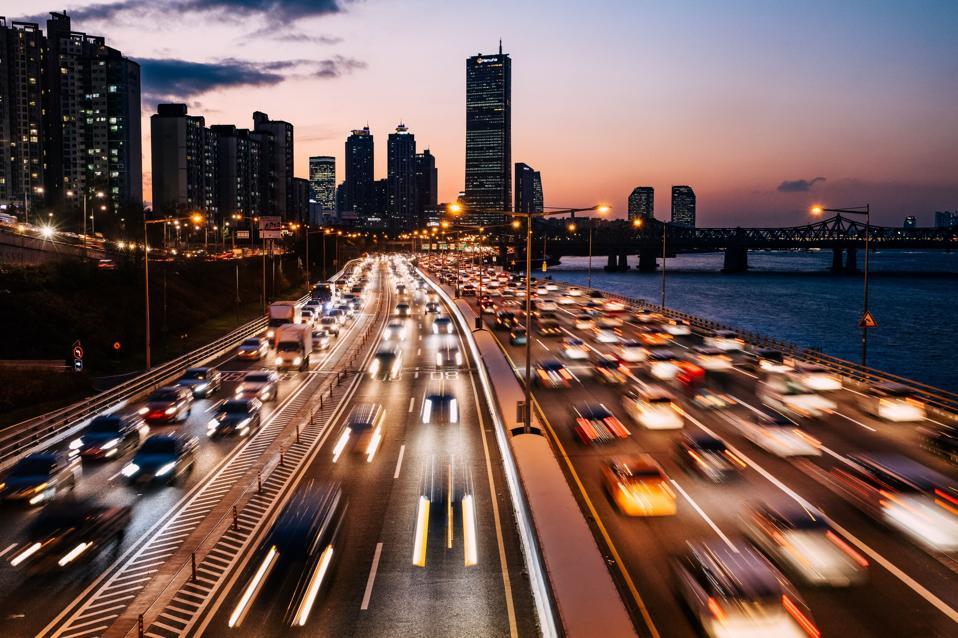 Autos speeding on highway at dusk.