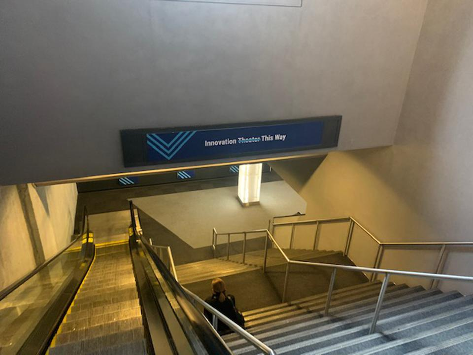 Photo of a staircase with a sign saying Innovation Theater This Way with Theater crossed out. Photo taken by Jules Miller at the CB Insights The Collective conference in New York, December 11, 2019