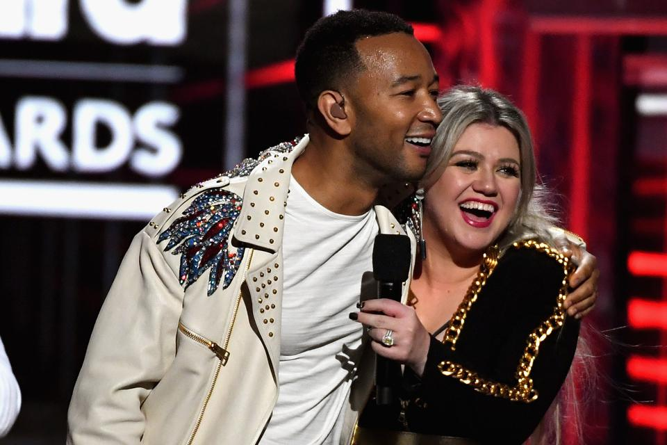 John Legend (L) and Kelly Clarkson (R) speak onstage during the 2018 Billboard Music Awards at MGM Grand Garden Arena on May 20, 2018
