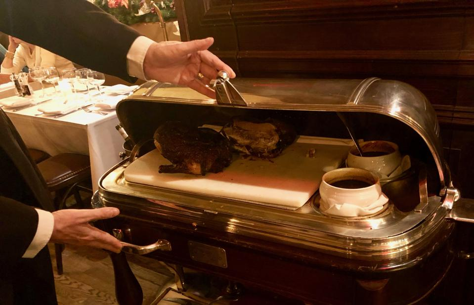 At La Goulue in New York, canard à l'orange awaits the carving knife under a silver plated dome.