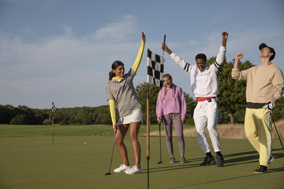 four golfers celebrate a put made on the practice green