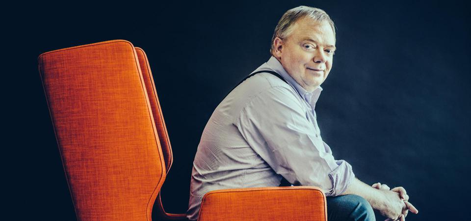 Anthony Wood founder of Roku poses for a photo in an orange chair.
