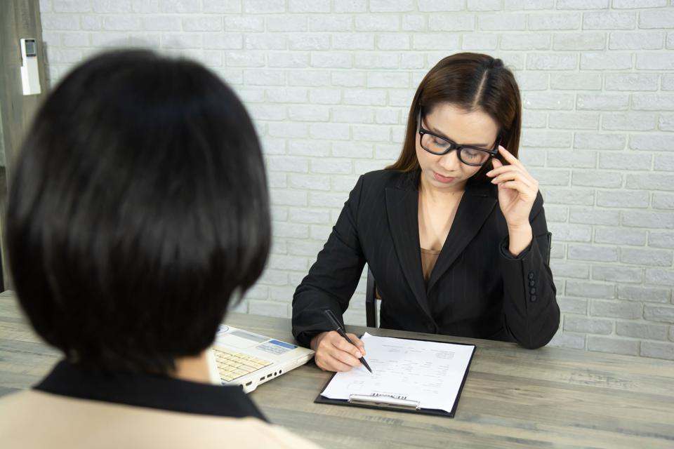 woman reviewing resume while interviewing another woman
