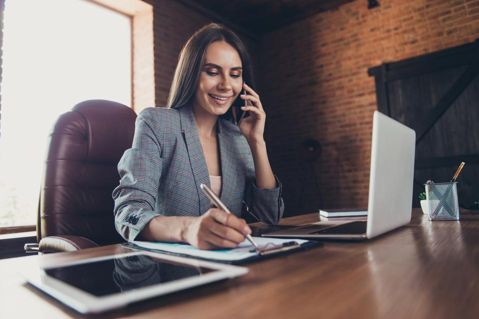 Successful lady in a gray checkered jacket speak on a cellular phone and writes down the order information on the form sit behind the desk in comfort loft workplace